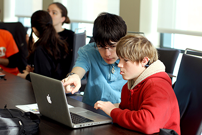 An older student peer-mentors a younger student on a coding project.