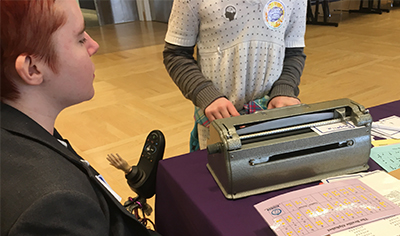A DO-IT staff member helps a student type out their name using a Perkins Brailler.