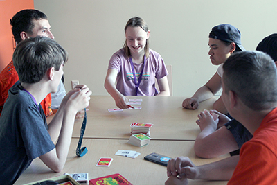 A group of Scholars play Apples to Apples in the dorm lounge during Summer Study 2018.