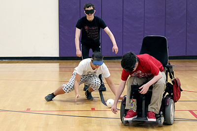 Scholars Ryan, Takashi, and Jonah try to locate the beeping baseball while wearing blindfolds during Summer Study.