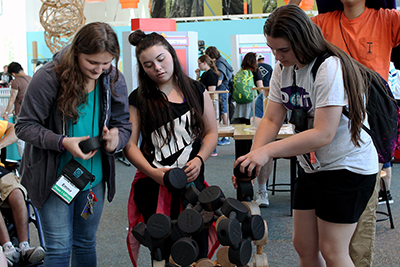 Phase I Scholars Emma and Hayley try out a hands-on Pacific Science Center exhibit with Intern, Brookelyn.