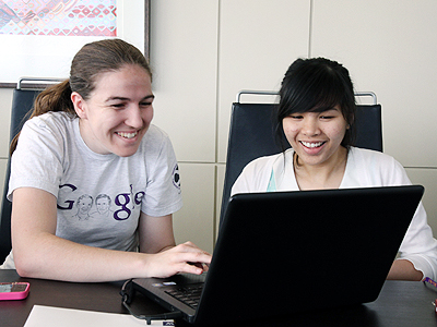 Photo of two women working on a project together using a computer