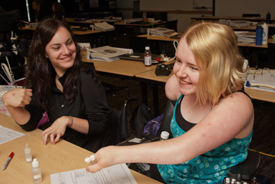 Photo of DO-IT Scholars McKenna and Kayla laughing while working on a science project during Summer Study 2013