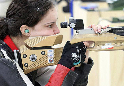Photo of McKenna looking through the viewfinder on a competition rifle
