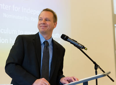 Photo of DO-IT program manager Scott Bellman standing at a podium to give an acceptance speech
