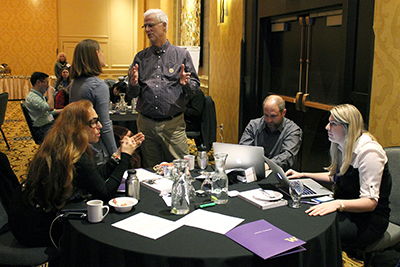 Two participants stand beside a table of three more, having multiple discussions.