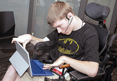 A student in a wheelchair uses a tablet with attachable keyboard.