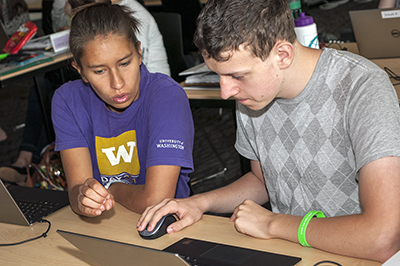 A student signs to another student while they work on a computer together.