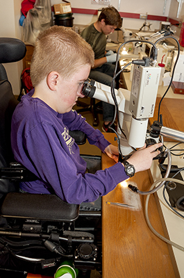 Student looks into microscope.