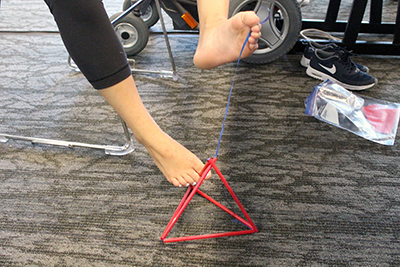 -	Phase I Scholar Teresa assembles a tetrahedron kite with her feet during Summer Study 2016.