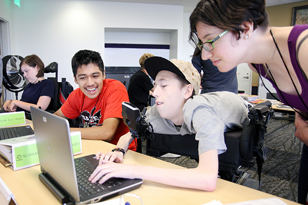 An intern helps two students complete a computing project.