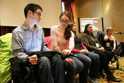 In the students with disabilities panel, Hannah holds the mic to Blake's assistive technology.