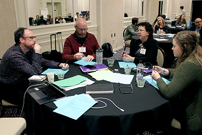 A group of conference participants discuss while sitting at a table.