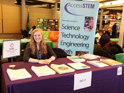 Photo of AccessSTEM Team member Jenica sitting behind the DO-IT booth at the 'See It. Be It' Conference.