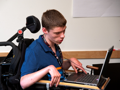 Photo of DO-IT Scholar Cody Hinkley using a laptop computer in his wheelchair