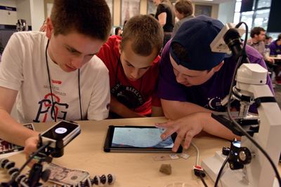 Three students with visual impairments look down at an enlarged screen on a tablet.