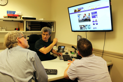 Hadi Rangin shows two UW faculty members how to make their website more accessible.