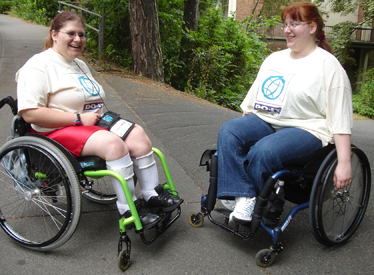 Photo of two students in wheelchairs outside on the UW campus.