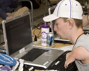Picture of student with mobility and hearing impairments working on his laptop.
