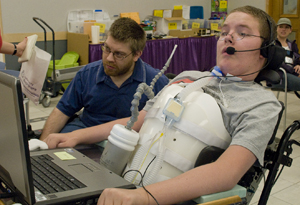 Photo of student in wheelchair at a laptop computer.