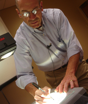 Photo of professor drawing on an overhead projector.