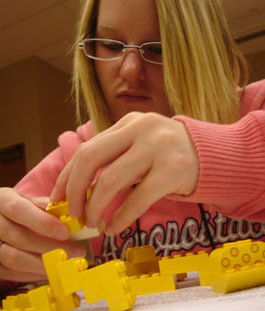 Student building a structure using LEGOS.
