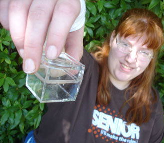 Picture of student holding insect in clear box.