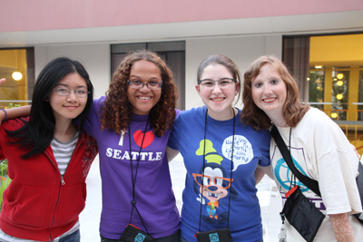 Photo of four DO-IT Scholars pose arm in arm outside UW's McCarty dorms during Summer Study 2012.