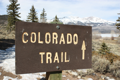 Photo of wood sign marking the Colorado Trail with pine trees and mountains in the background.