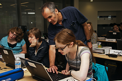 A mentor assists a participant with a computing project.