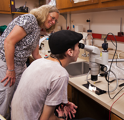 A participant examines a biology specimen through a microscope while a mentor watches.