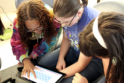 A group of students do an activity on a tablet.