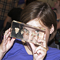 A student looks through a transparent depiction of brains.