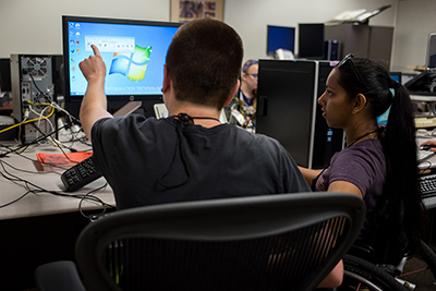 Two students working together on a computer.