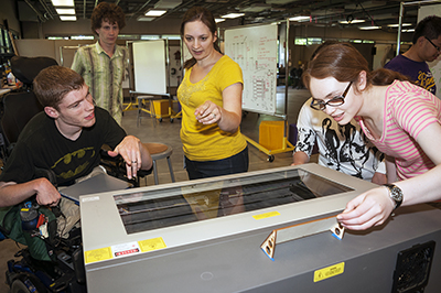 DO-IT Staff Brianna shows 3 students a piece of equipment in the UW CoMotion Makerspace.