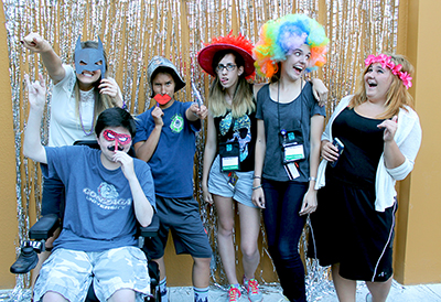 One DO-IT Staff member and five Scholars pose in silly ways wearing silly hats and masks in front of a sparkly background