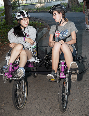 DO-IT Phase I Scholars Chana and Katelyn share a laugh while riding an accessible bike together.