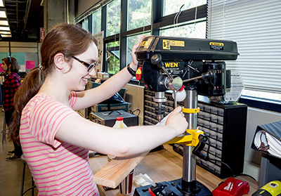 DO-IT Intern Hannah puts a piece of wood into a machine in the UW CoMotion Makerspace.