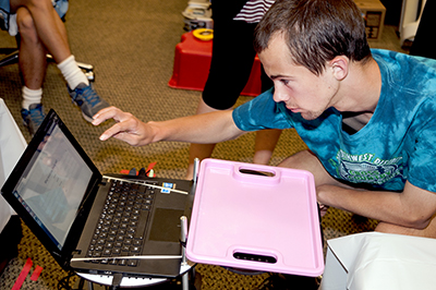 Phase Two Scholar Jason touches a laptop attached to a machine, which is Chester, the Turtlebot.