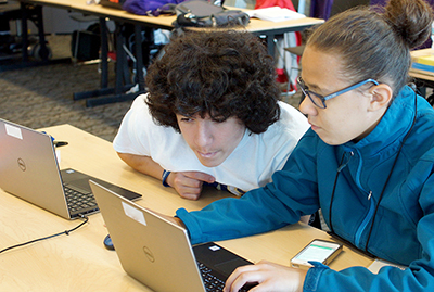 Two students working together on computers editing web-based text.