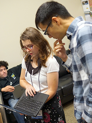 A mentor helps a student with a computing project.