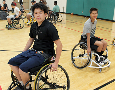 Two students use sports wheelchairs.