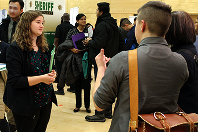 An interpreter works with a student at a career fair.