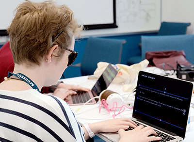 A student with a visual disability codes on a computer during last year's OurCS workshop.