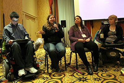 A panel of students with disabilities talk in front of the room.