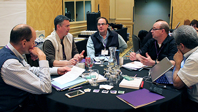 A group of participants speak together around a table.
