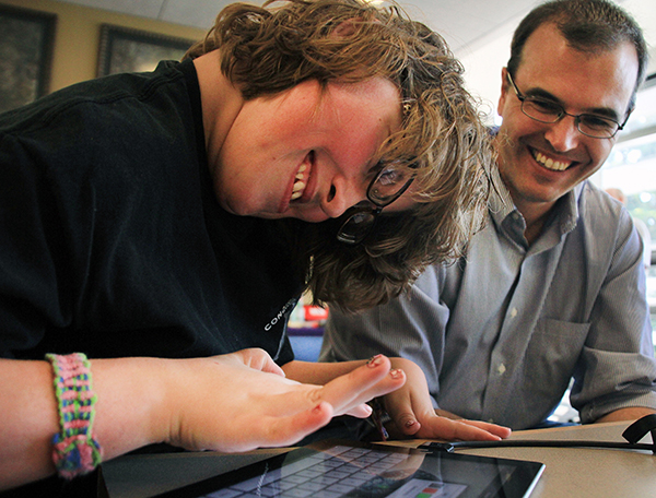 An instructor works with a student on a tablet.