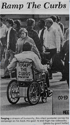 "A newspaper clipping showing a man in a wheelchair with ""Ramp the Curbs""on the back of his chair"