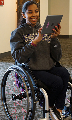 A female student in a wheelchair uses a tablet.