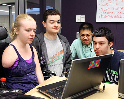 Image of a group of students collaborating on a laptop